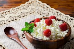 Cottage cheese with fresh raspberry in a wooden bowl on old wood. En background with copy space for your text. Top view Royalty Free Stock Image