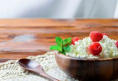 Cottage cheese with fresh raspberry in a wooden bowl on old wood. En background with copy space for your text. Top view Stock Images