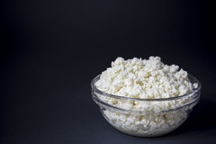 Cottage cheese in a glass bowl. Background. Space for text. White fresh cheese in a glass bowl on a dark background. Contrast image, background, space for text Royalty Free Stock Image