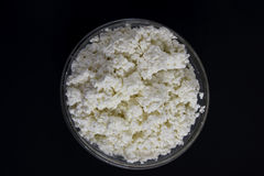 Cottage cheese in a glass bowl. Background. White fresh cheese in a glass bowl on a dark background. Contrast image, background, space for text Royalty Free Stock Photography