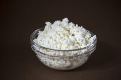 Cottage cheese in a glass bowl. Brown background. White fresh cheese in a glass bowl on a brown background. Contrast image, background, space for text Stock Photos