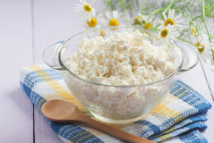 Cottage cheese in a glass container, a wooden spoon and chamomil Royalty Free Stock Image