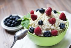 Cottage cheese in green bowl with raspberries and blueberries on wooden background. Healthy Breakfast. Cottage cheese in green bowl with raspberries  and Stock Image