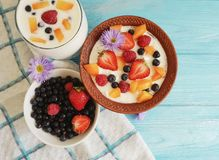 Cottage cheese healthy dessert diet yogurt, strawberry, apricot, blueberry on a blue background, flower. Cottage cheese yogurt, strawberry, apricot, blueberry on royalty free stock image