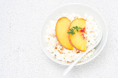 Cottage cheese with honey, nuts, fresh peaches and thyme Stock Image