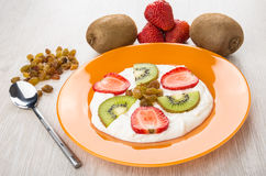 Cottage cheese with kiwi, strawberry and raisin in plate, spoon Stock Image