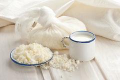 Cottage cheese and milk for breakfast. Fresh organic handmade cheese in cheesecloth and milk in vintage cup Stock Photo