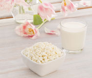 Cottage cheese with milk and pink tulips. Cottage cheese with milk and pink  and white terry tulips Royalty Free Stock Images