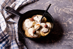 Cottage cheese pancakes with banana slices in frying pan, Royalty Free Stock Photography