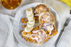 Cottage cheese pancakes with banana slices and sea buckthorn ber Stock Images