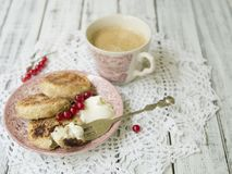 Cottage cheese pancakes with berries and sour cream, cup of black coffee, tasty breakfast royalty free stock photography