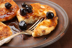 Cottage cheese pancakes. With cherry conserve on brown plate Royalty Free Stock Photo