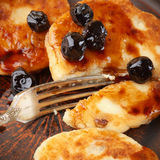 Cottage cheese pancakes. With cherry conserve on brown plate Stock Image