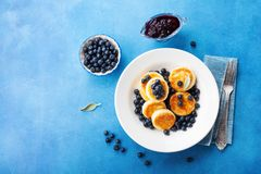 Cottage cheese pancakes or curd fritters decorated honey and blueberry in plate on blue table top view. Healthy and diet breakfast.  stock photo