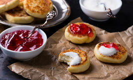 Cottage cheese pancakes with currant jam and sour cream. Selective focus stock images