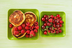 Cottage cheese pancakes with fresh raspberries and cherry on the green plates on the green wooden background. Stock Images