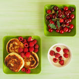 Cottage cheese pancakes with fresh raspberries, cherry and sour cream on the green plates on the green wooden background, top view. Square photo Stock Photo