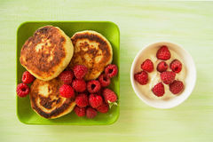 Cottage cheese pancakes with fresh raspberries and sour cream on the green and white plates on the green wooden background. Royalty Free Stock Photo