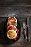 Cottage cheese pancakes with raspberries on old iron pan. Style rustic. Selective focus Stock Photos