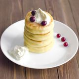 Cottage cheese pancakes with sour cream and berries on rustic ba stock images