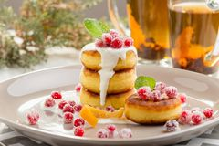 Cottage cheese pancakes with sour cream and cranberry. Cottage cheese pancakes with sugared cranberry and sour cream or yogurt. Russian syrniki. Homemade stock photos