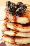 Cottage cheese pancakes. Stack of cottage cheese pancakes with cherry conserve on wooden background Stock Image