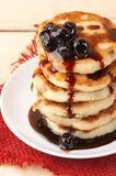 Cottage cheese pancakes. Stack of cottage cheese pancakes with cherry conserve on wooden background Royalty Free Stock Image