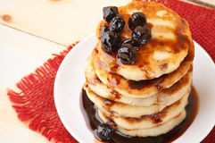 Cottage cheese pancakes. Stack of cottage cheese pancakes with cherry conserve on wooden background Stock Photos