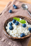 Cottage cheese (quark) with blueberries. Cottage cheese (quark) with fresh blueberries decorated with mint leaf. Healthy country breakfast. Vertical Stock Images