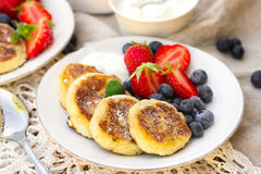 Cottage cheese quark pancakes syrniki with fresh berries. Cottage cheese quark pancakes syrniki with strawberry and blueberry Royalty Free Stock Images
