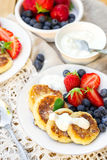 Cottage cheese quark pancakes syrniki with fresh berries. Cottage cheese quark pancakes syrniki with strawberry and blueberry Stock Images