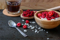 Cottage cheese with raspberries and cup of coffee for breakfast. With scattered berries and grains of curd Stock Images