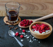 Cottage cheese with raspberries and cup of coffee. For tasty breakfast. with scattered berries, grains of curd and coffee beans Royalty Free Stock Photography