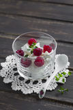 Cottage cheese with raspberries and thyme in a glass beaker. On a dark wooden surface Royalty Free Stock Photo