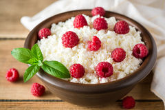 Cottage cheese with raspberry and mint in ceramic bowl on rustic wooden table Royalty Free Stock Image