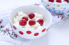 Cottage cheese with raspberry in white bowl of peas. On a towel with embroidery Royalty Free Stock Images