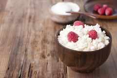 Cottage cheese with raspberry in wooden bowl. Home cottage cheese with raspberry in wooden bowl on old wooden table Stock Photos
