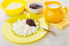 Cottage cheese, spoon with raspberry jam in plate, yogurt Stock Images