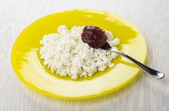Cottage cheese, spoon with raspberry jam in yellow plate Royalty Free Stock Images