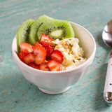 Cottage cheese with strawberries, kiwi, honey and flax seeds - healthy Breakfast in a white bowl Royalty Free Stock Photos