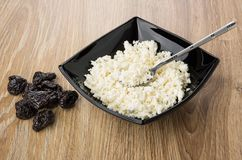 Cottage cheese and teaspoon in black bowl, heap of prunes. On wooden table royalty free stock photo