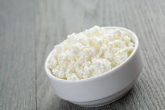 Cottage cheese in white bowl on old table Royalty Free Stock Photo