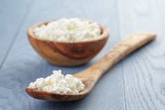 Cottage cheese in wood bowl on blue wooden table Stock Photo