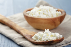 Cottage cheese in wood bowl on blue wooden table Royalty Free Stock Photography