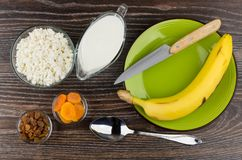 Cottage cheese, yogurt, bananas, dried fruits, knife and spoon Royalty Free Stock Photos