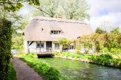 Cottage couvert de chaume anglais au-dessus de rivière débordante Photographie stock