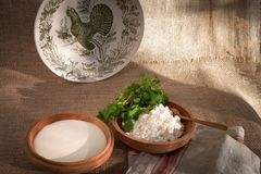 Cottage curd and sour cream in wooden bowls with parsley and cilantro Stock Photos