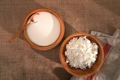 Cottage curd and sour cream in wooden plate on a linen tablecloth Stock Image