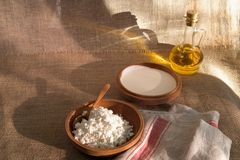 Cottage curd and sour cream in wooden plate on a linen tablecloth Royalty Free Stock Photo