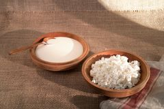 Cottage curd and sour cream in wooden plate on a linen tablecloth Stock Photo